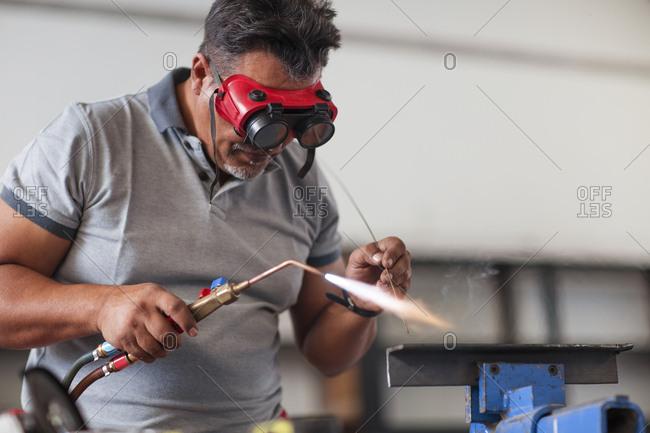 Mechanic welding in car workshop