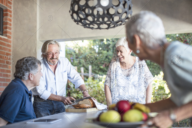 Two happy senior couples together on terrace