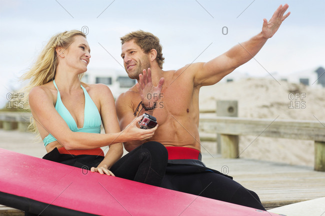 Happy couple with surfboard talking on the beach