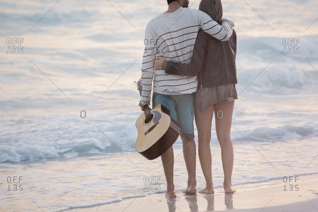 Young couple looking at the sea with arms around