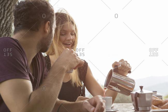 Couple having breakfast outdoors - Offset