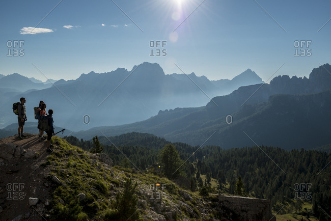 Italy- Friends standing on mountain top in the Dolomites- looking at view