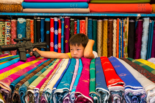 Ulan Baatar, Mongolia - August 21, 2015: Boy playing with a plastic Gun - Narantuul Market in Ulaan Baatar, Mongolia