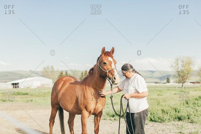 Umatilla Reservation, Pendleton, Oregon - May 10, 2017: Woman petting brown horse
