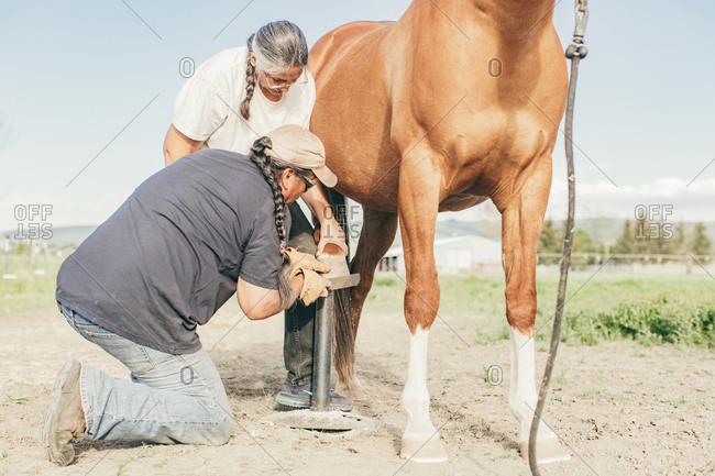 Umatilla Reservation, Pendleton, Oregon - May 10, 2017: Couple filing horse's hooves