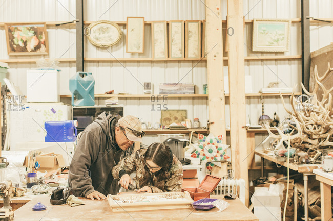 Umatilla Reservation, Pendleton, Oregon - May 17, 2017: Daughter and father working together in a workshop