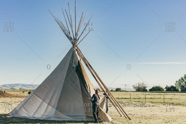 Umatilla Reservation, Pendleton, Oregon - May 18, 2017: Couple setting up a tipi
