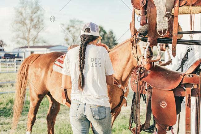 Umatilla Reservation, Pendleton, Oregon - May 18, 2017: Girl preparing to ride horse on the Umatilla Reservation in Oregon