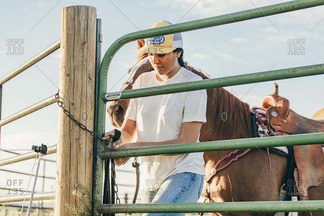 Umatilla Reservation, Pendleton, Oregon - May 18, 2017: Girl opening horse pen on the Umatilla Reservation in Oregon