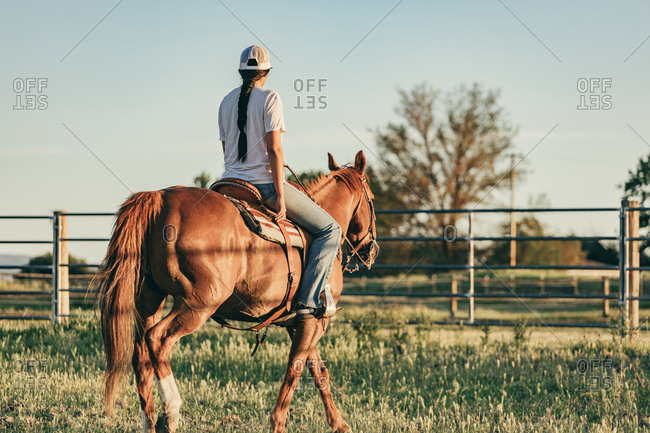 Umatilla Reservation, Pendleton, Oregon - May 18, 2017: Rear view of girl riding brown horse on the Umatilla Reservation in Oregon