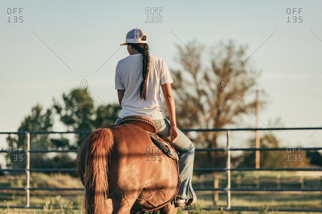 Umatilla Reservation, Pendleton, Oregon - May 18, 2017: Back view of girl riding brown horse on the Umatilla Reservation in Oregon