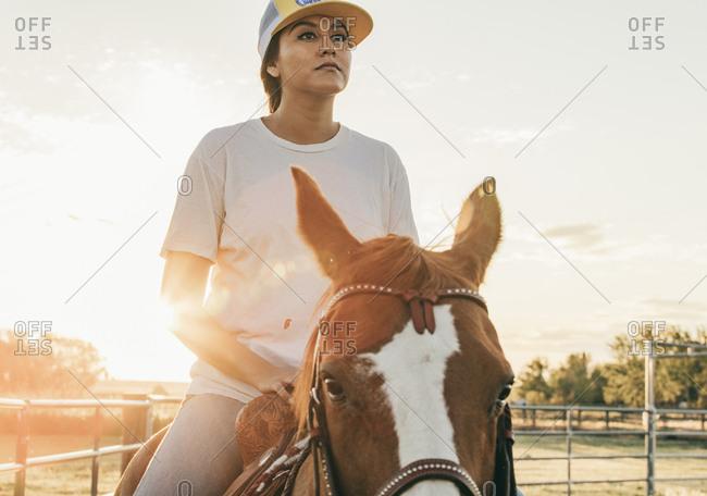 Umatilla Reservation, Pendleton, Oregon - May 18, 2017: Girl riding horse on the Umatilla Reservation in Oregon at sunset