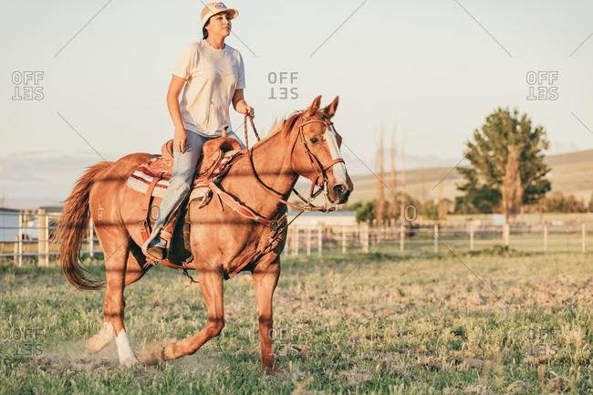 Umatilla Reservation, Pendleton, Oregon - May 18, 2017: Girl riding brown horse on the Umatilla Reservation in Oregon at sunset