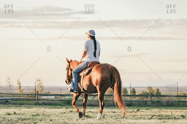 Umatilla Reservation, Pendleton, Oregon - May 18, 2017: Rear view of girl riding a horse on the Umatilla Reservation in Oregon