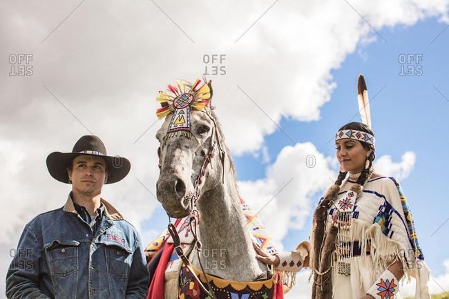 Umatilla Reservation, Pendleton, Oregon - May 14, 2017: Native American young woman dressed in regalia with horse and a cowboy