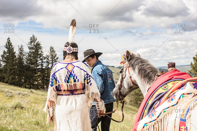 Umatilla Reservation, Pendleton, Oregon - May 14, 2017: Native American young woman dressed in regalia walking with horse beside a cowboy