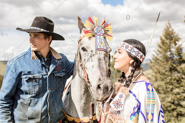 Umatilla Reservation, Pendleton, Oregon - May 14, 2017: Young Native American woman dressed in regalia standing with a cowboy and horse