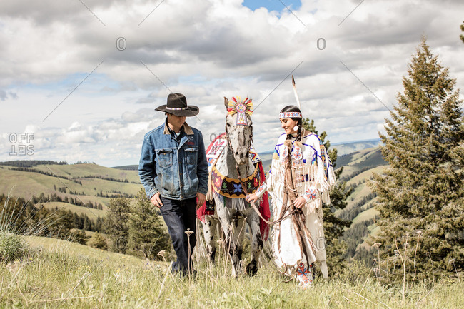 Umatilla Reservation, Pendleton, Oregon - May 14, 2017: Young Native American woman dressed in regalia walking with a cowboy and horse