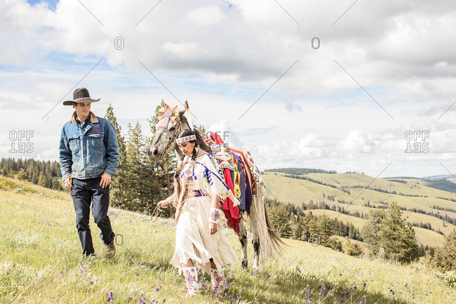 Umatilla Reservation, Pendleton, Oregon - May 14, 2017: Young Native American woman in regalia walking with a cowboy and a horse