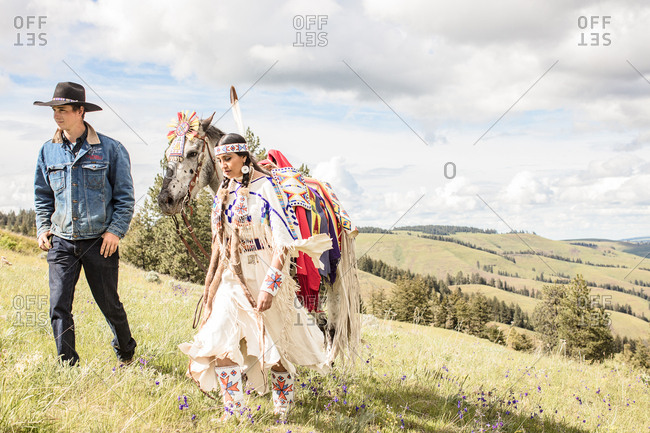 Umatilla Reservation, Pendleton, Oregon - May 14, 2017: Young Native American woman in regalia walking with a horse and a cowboy
