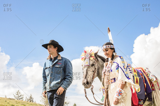 Umatilla Reservation, Pendleton, Oregon - May 14, 2017: Cowboy walking with a young Native American woman in regalia and her horse