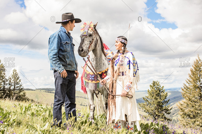 Umatilla Reservation, Pendleton, Oregon - May 14, 2017: Cowboy standing with a young Native American woman in regalia and her horse