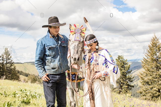 Umatilla Reservation, Pendleton, Oregon - May 14, 2017: Cowboy and a young Native American woman in regalia with her horse
