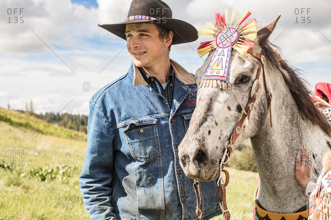 Umatilla Reservation, Pendleton, Oregon - May 14, 2017: Cowboy standing beside a young Native American woman and her horse