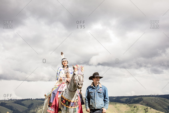Umatilla Reservation, Pendleton, Oregon - May 14, 2017: Native American young woman dressed in regalia riding horse beside a cowboy