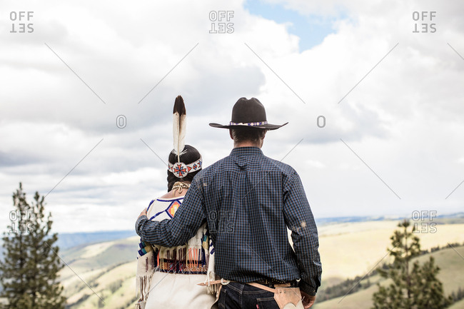 Umatilla Reservation, Pendleton, Oregon - May 14, 2017: Rear view of cowboy standing with arm around Native American woman dressed in regalia