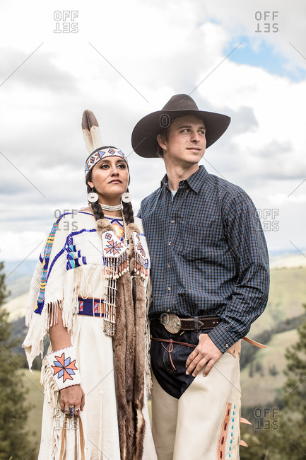 Umatilla Reservation, Pendleton, Oregon - May 14, 2017: Cowboy standing with arm around Native American woman dressed in regalia