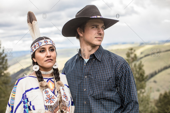 Umatilla Reservation, Pendleton, Oregon - May 14, 2017: Close up of cowboy standing with arm around Native American woman dressed in regalia