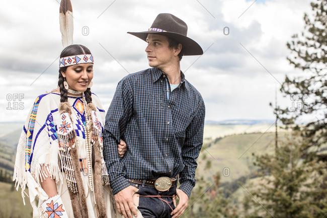 Umatilla Reservation, Pendleton, Oregon - May 14, 2017: Cowboy walking with Native American woman dressed in regalia