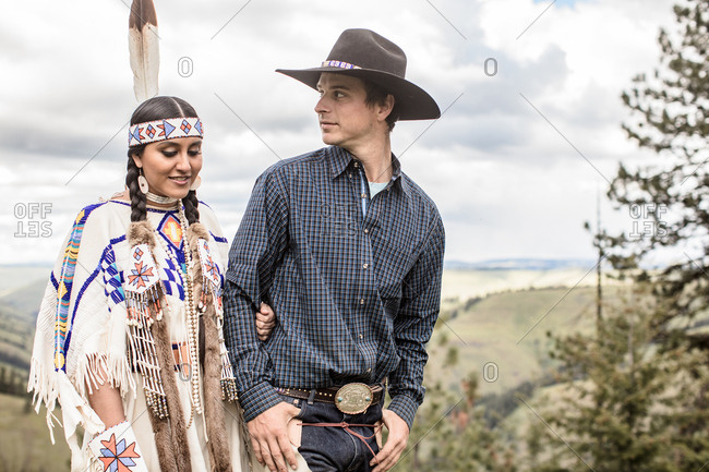 Umatilla Reservation, Pendleton, Oregon - May 14, 2017: Cowboy walking with Native American woman dressed in regalia