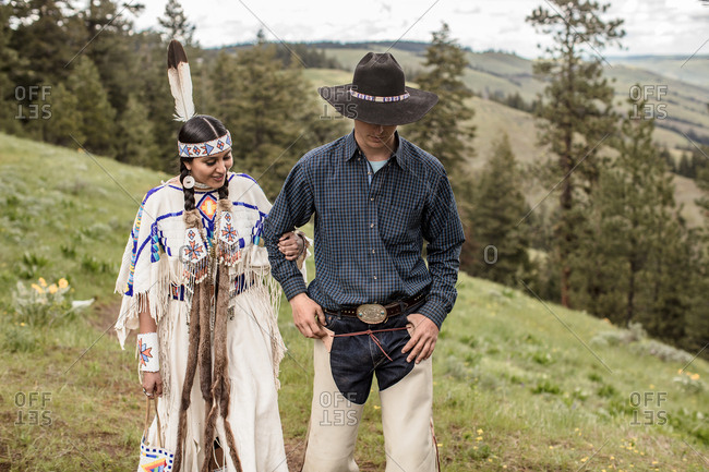 Umatilla Reservation, Pendleton, Oregon - May 14, 2017: Cowboy walking arm in arm with Native American woman dressed in regalia