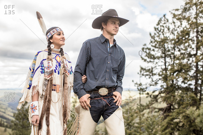 Umatilla Reservation, Pendleton, Oregon - May 14, 2017: Cowboy walking with Native American woman dressed in regalia on the Umatilla Reservation in Oregon