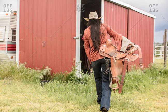 Umatilla Reservation, Pendleton, Oregon - May 13, 2017: Young woman carrying horse saddle into a shed