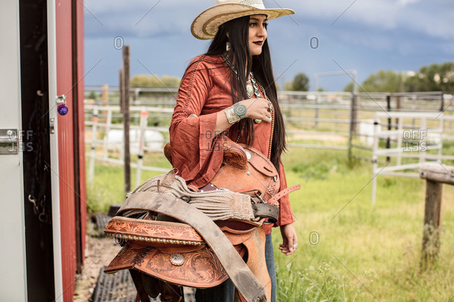 Umatilla Reservation, Pendleton, Oregon - May 13, 2017: Young woman holding a horse saddle