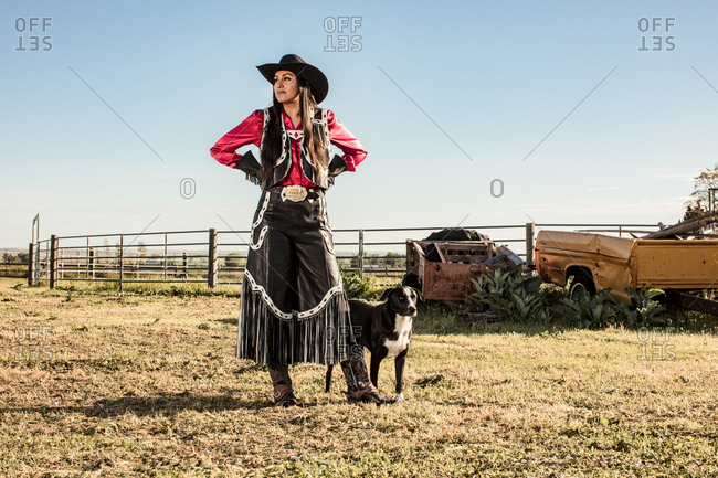 Umatilla Reservation, Pendleton, Oregon - May 18, 2017: Young woman dressed in cow girl attire with dog on a Native American Reservation