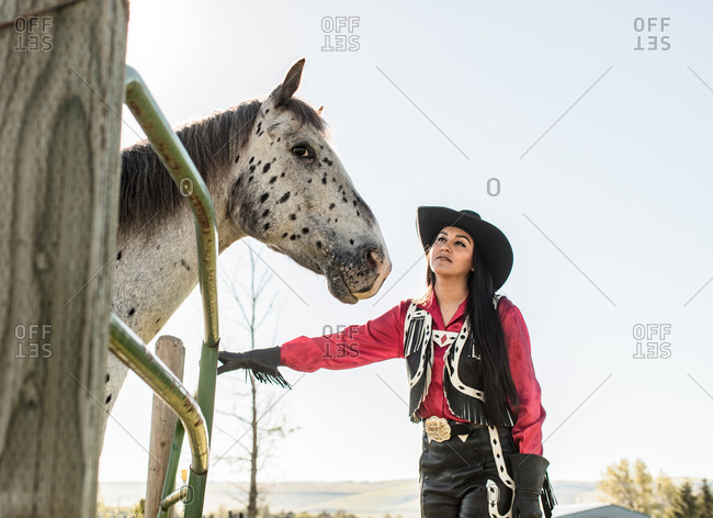 Umatilla Reservation, Pendleton, Oregon - May 18, 2017: Girl dressed in cow girl attire looking at a spotted horse