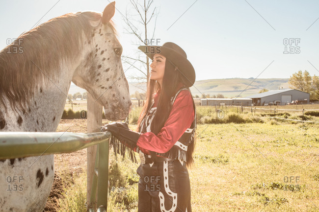Umatilla Reservation, Pendleton, Oregon - May 18, 2017: Young woman dressed in cow girl attire looking at a spotted horse