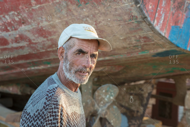 Essaouira, Morocco - June 20, 2017: Older man standing by boat