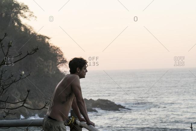 Man overlooking ocean from balcony