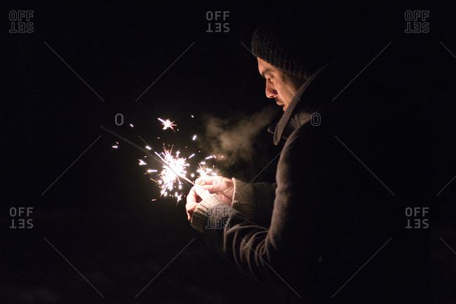 Man holding a lit sparkler