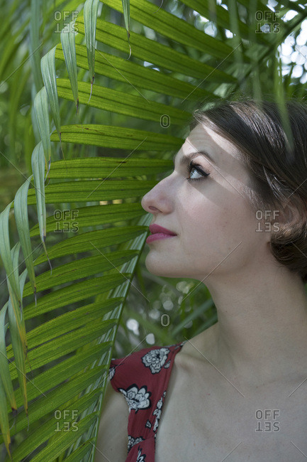 Beautiful woman in shade of palm leaf