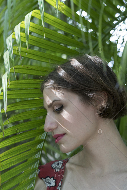 Portrait of a woman in the shade of a palm leaf