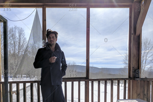 Man smoking on screened porch in winter