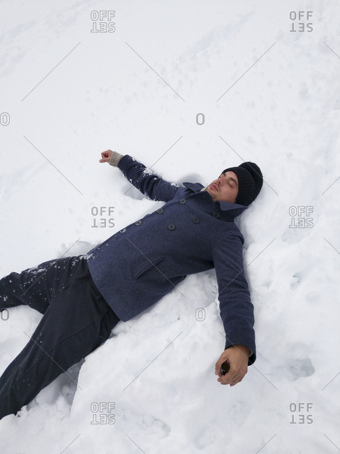 Man lying on back in snow