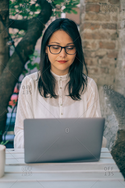 Young woman typing on computer at outdoor cafe
