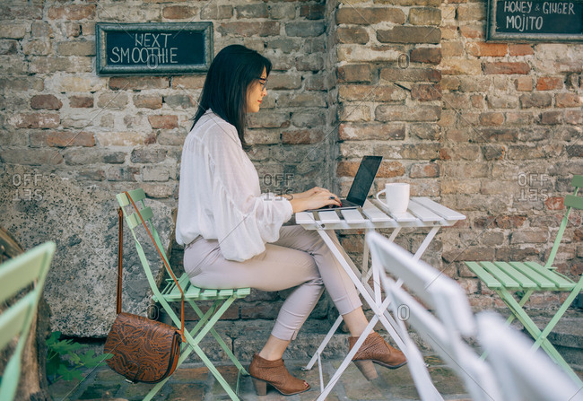 Woman using computer at cafe table by brick wall